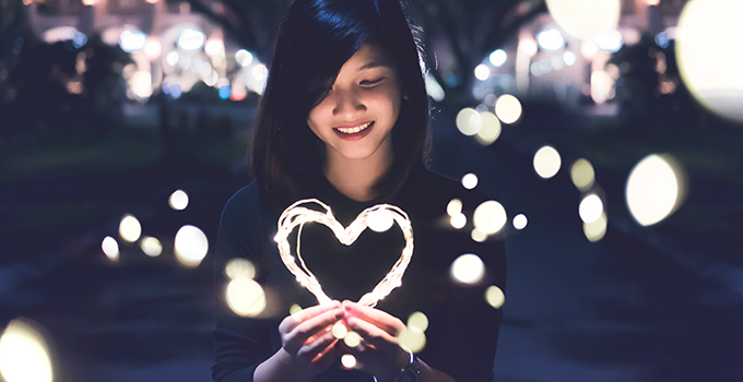 Student holding a virtual heart made of light