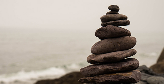 Image of stacked rocks against an ocean background.