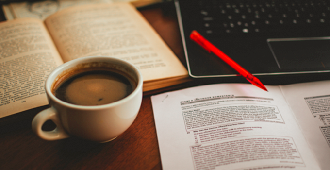 image of printed notes, coffee mug, and a laptop